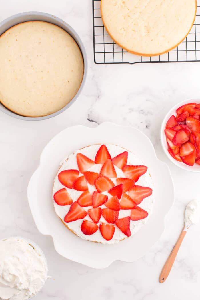 first layer of cake topped with whipped cream and sliced strawberries