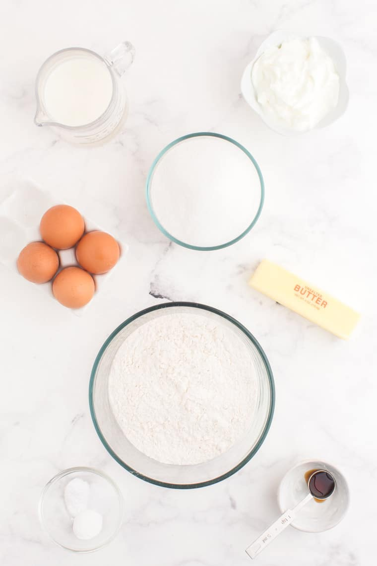 Gluten free flour, baking soda, baking powder, vanilla extract, eggs, butter, sugar, milk, and Greek yogurt in bowls and containers on a table