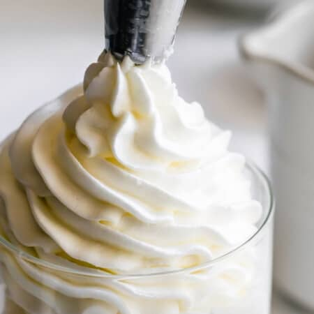 vanilla buttercream coming our of the star tip of a piping bag into a jar