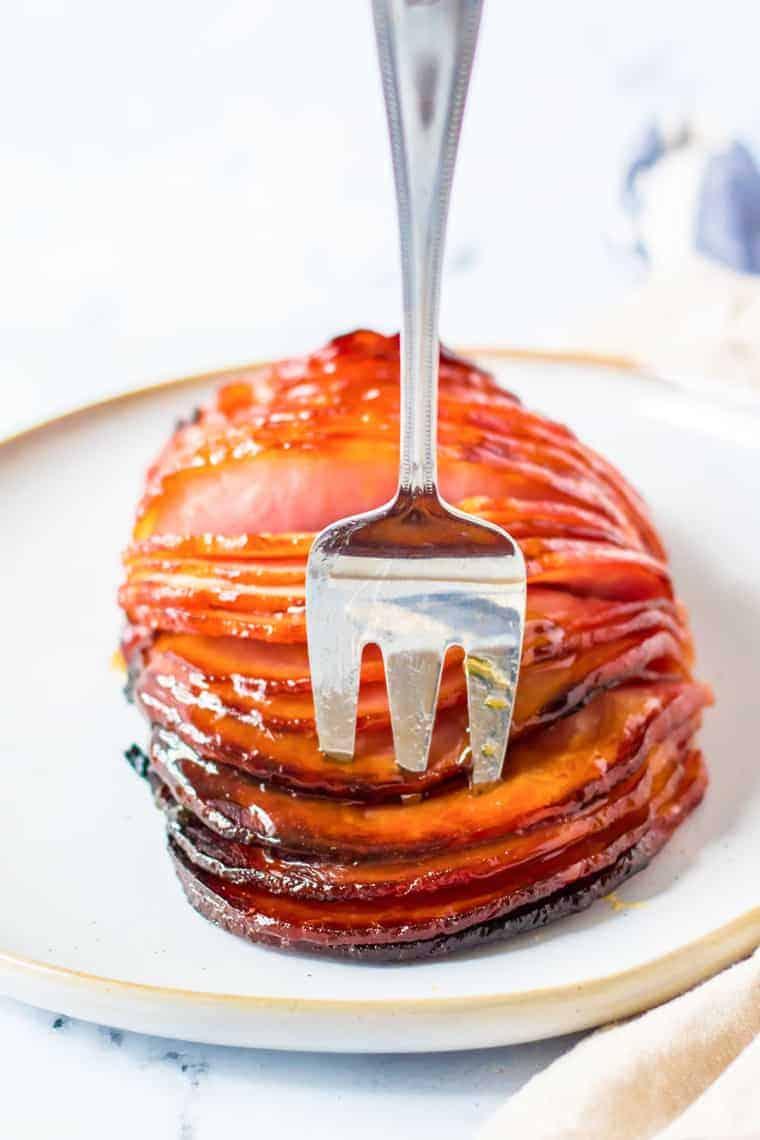 meat fork in a sliced boneless ham