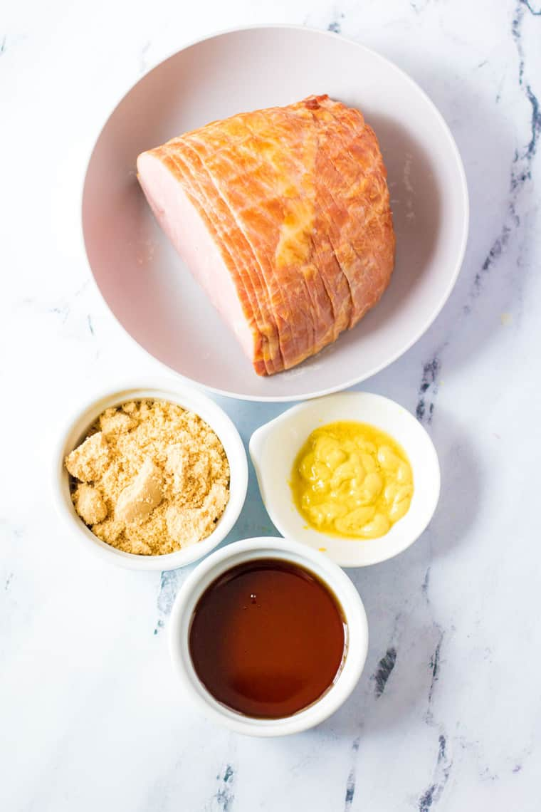 boneless ham on a plate with bowls of maple syrup, brown sugar, and Dijon mustard