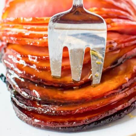 meat fork in sliced of glazed boneless ham