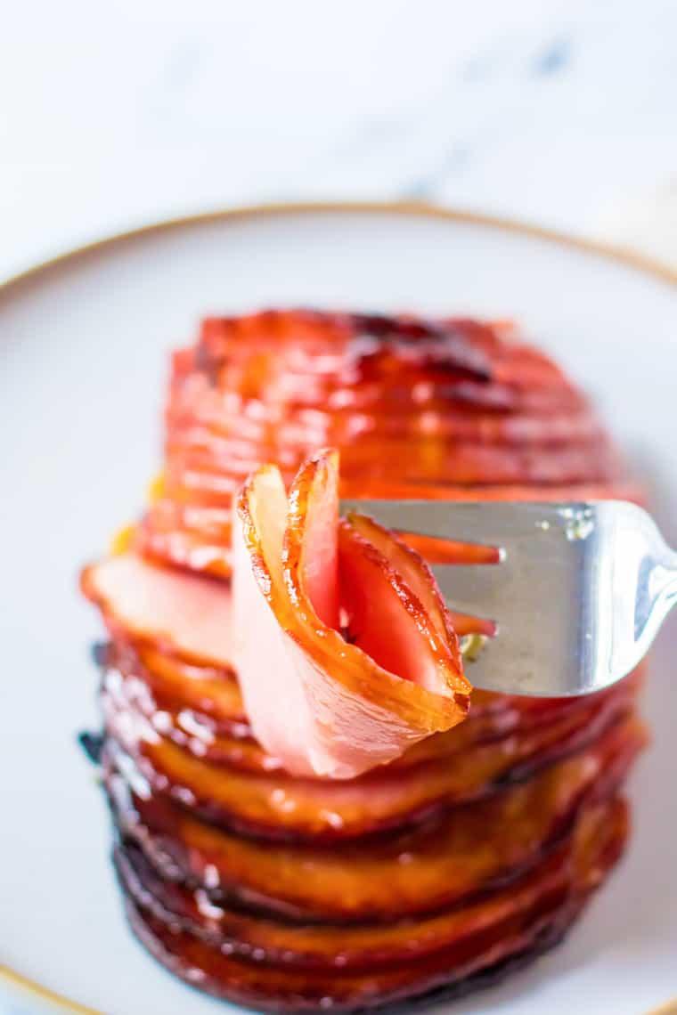 meat fork holding a folded slice of ham