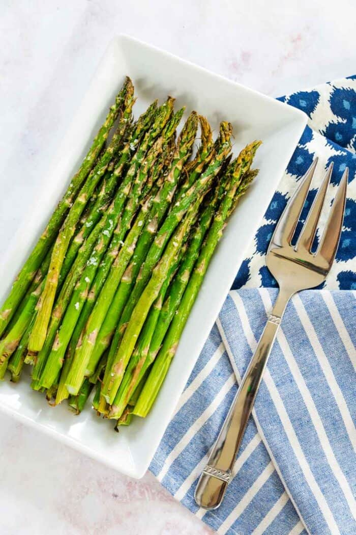 air fryer asparagus on a white rectangular plate with a serving fork