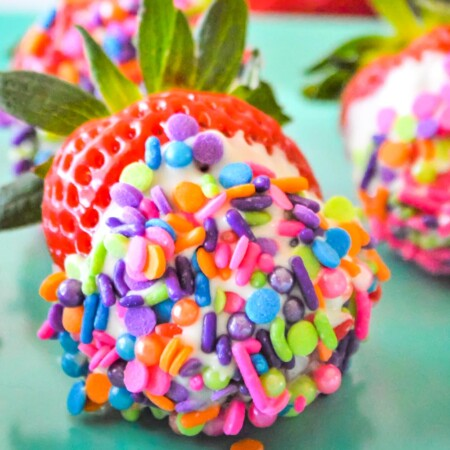 rainbow sprinkles covering a white chocolate dipped strawberry