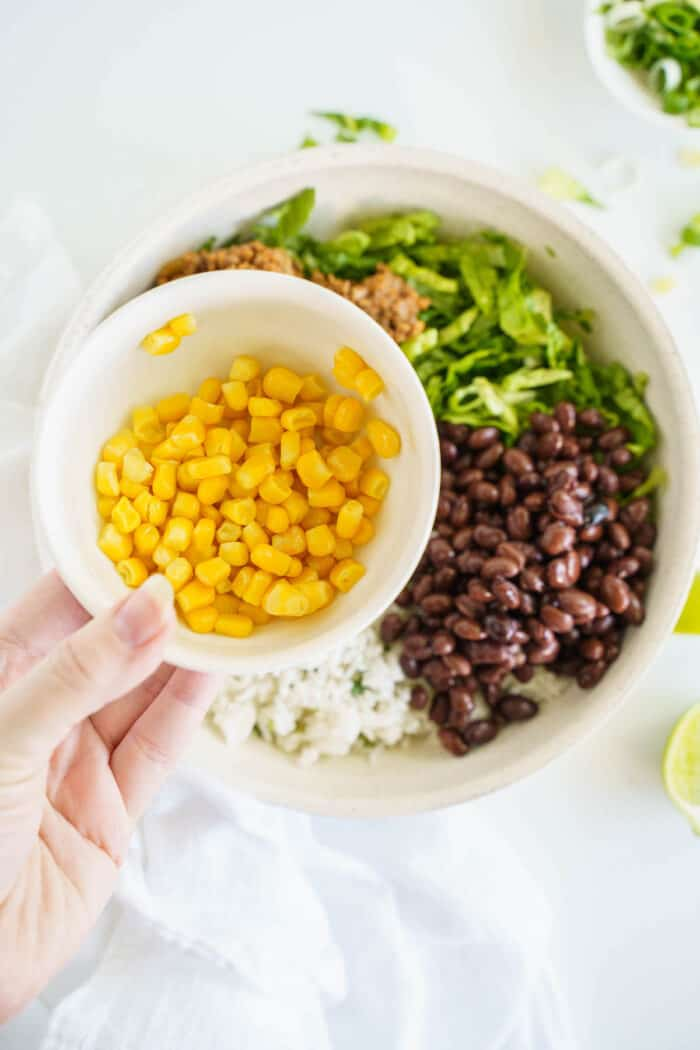 A Dish of Corn Hovering Over a Burrito Bowl in the Process of Being Assembled