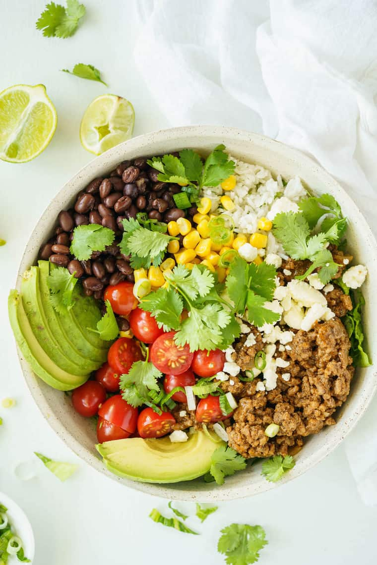 The Top View of a Beef Burrito Bowl Next to Two Lime Wedges