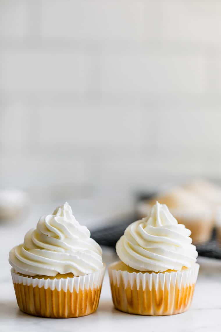 Two Gluten Free Vanilla Cupcakes Topped with Vanilla Buttercream