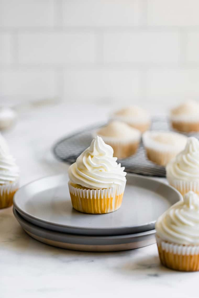 A Gray Plate Containing a Vanilla Cupcake with Unfrosted Cupcakes on a Wire Rack in the Background