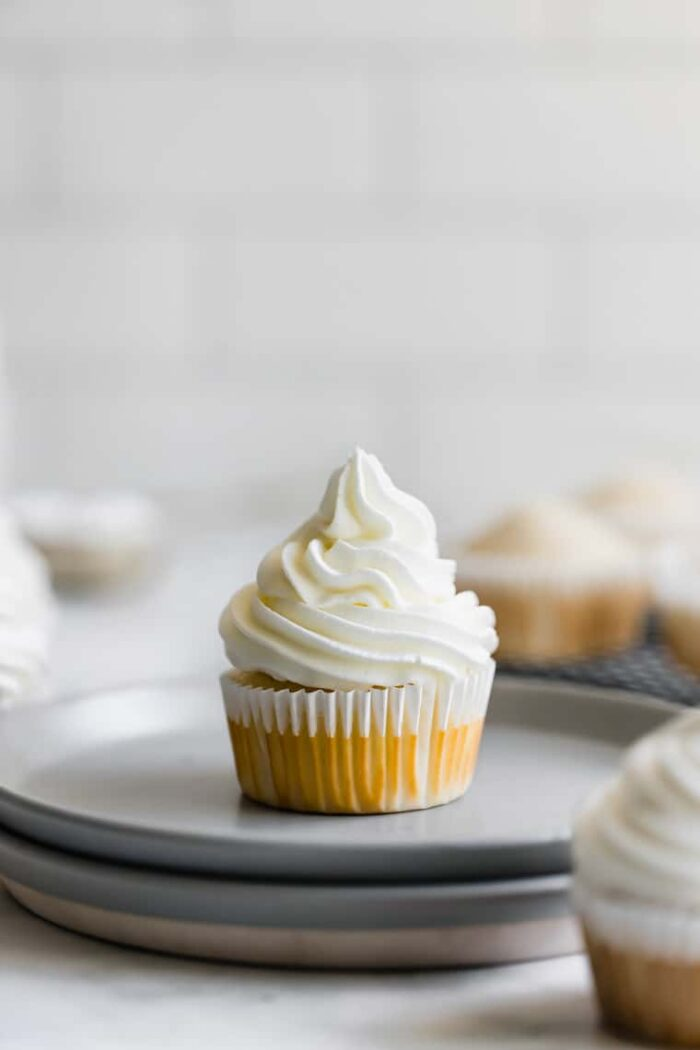 A Single Vanilla Cupcake with Vanilla Frosting on Two Stacked Plates