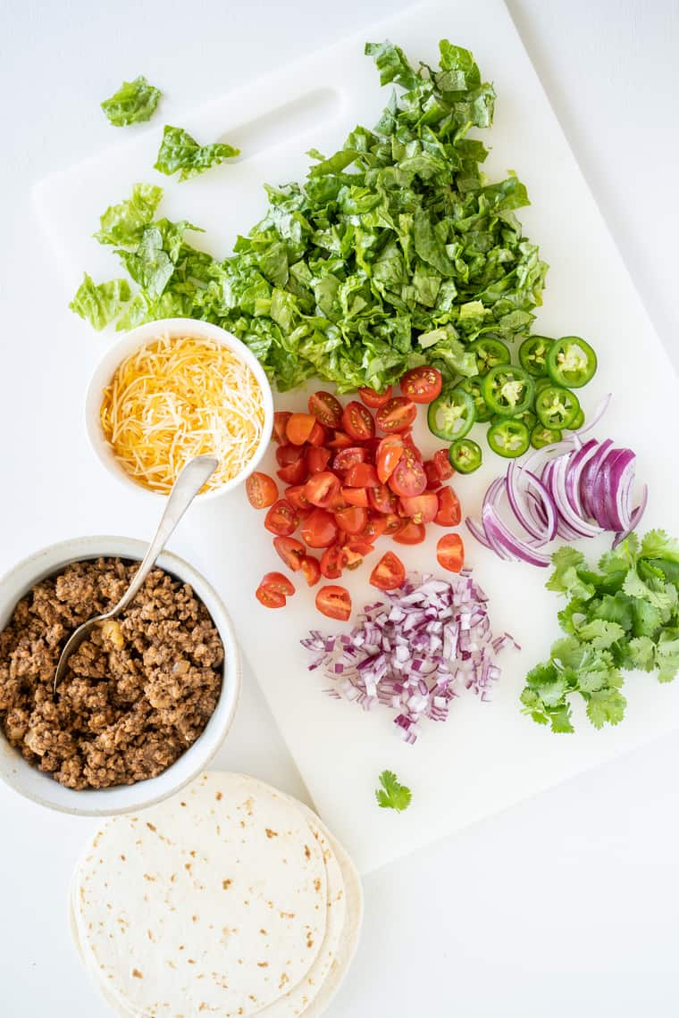 Bowls of Taco Meat, Cheese and Tortillas Next to Various Vegetables on a Cutting Board