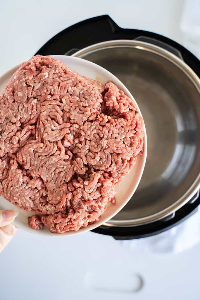 A Plate of Raw Ground Beef Being Held Over an Empty Instant Pot