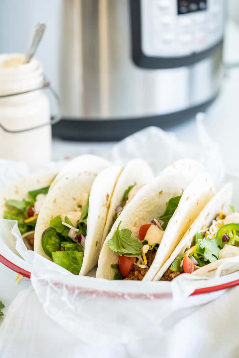 tacos on a plate near an Instant Pot