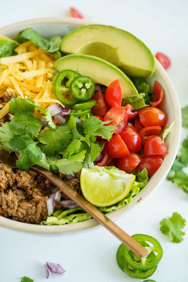 A Deconstructed Taco with Chopped Tomatoes, Avocado and Shredded Cheese in a Dish