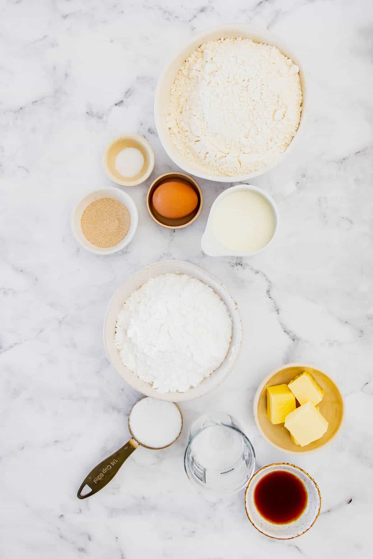 Gluten-Free Flour, Powdered Sugar, Butter, and the Rest of the Air Fryer Donut and Glaze Ingredients on a Marble Counter
