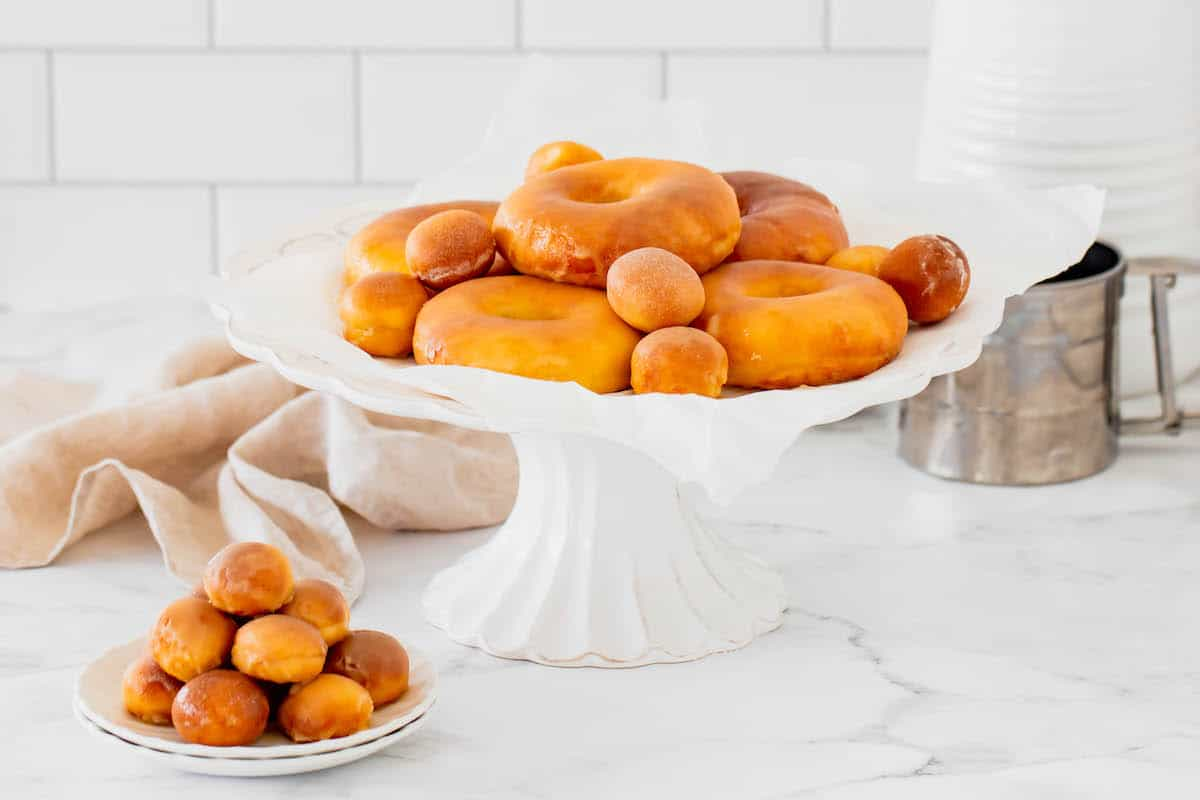 Air Fryer Donuts and Donut Holes on a Cake Stand Next to a Bowl of Donut Holes