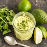 jar of avocado crema on a slate counter surrounded by an avocado, limes and a bunch of cilantro