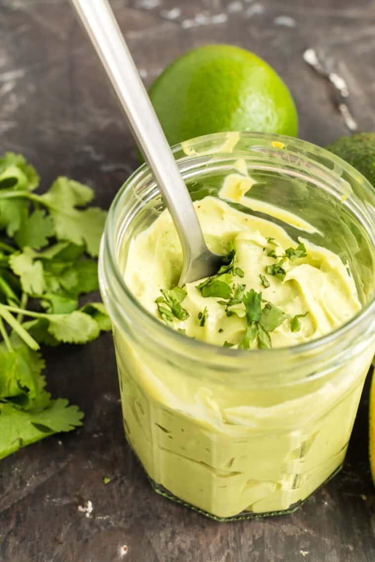 spoon in a jar of avocado crema with a garnish of cilantro on top
