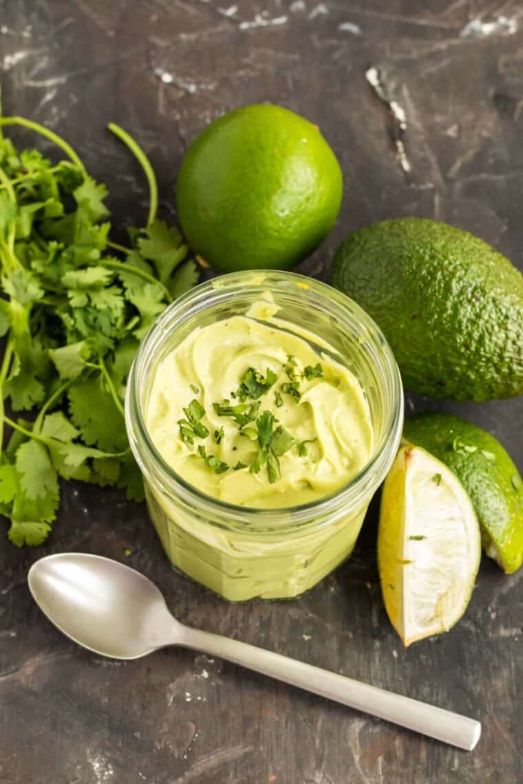 jar of avocado cream surrounded by an avocado, limes and a bunch of cilantro