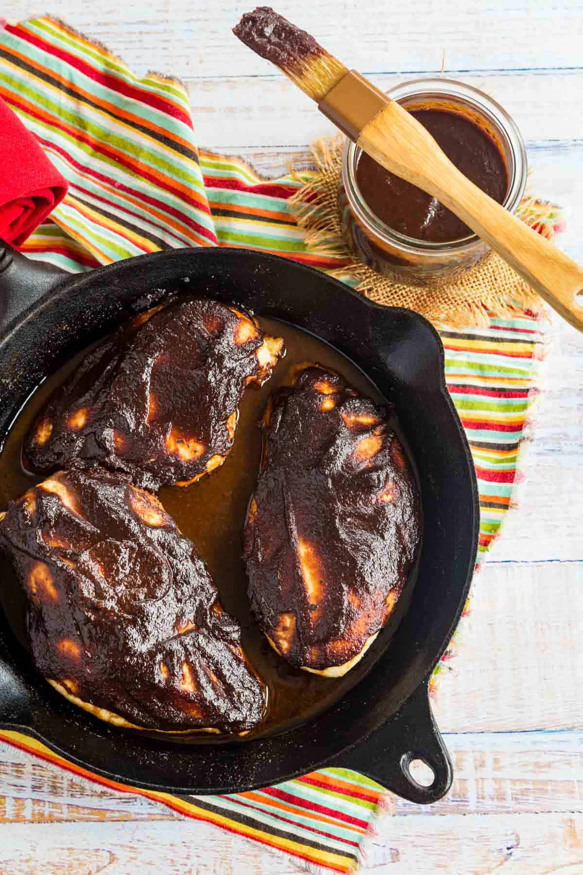 three baked chicken breasts covered in BBQ sauce in a skillet next to a jar of balsamic barbecue sauce