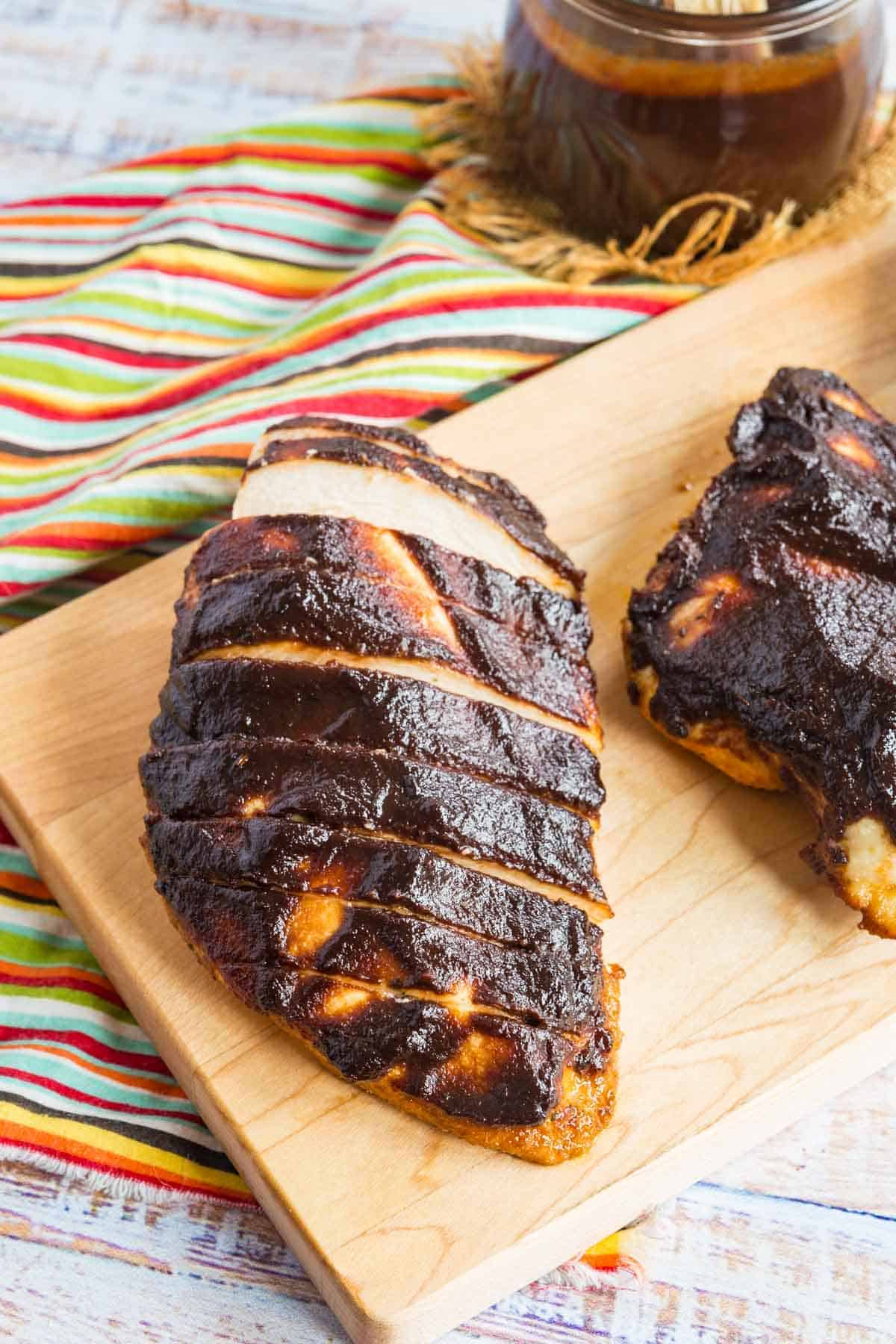 bbq balsamic baked chicken breast cut into slices on a cutting board