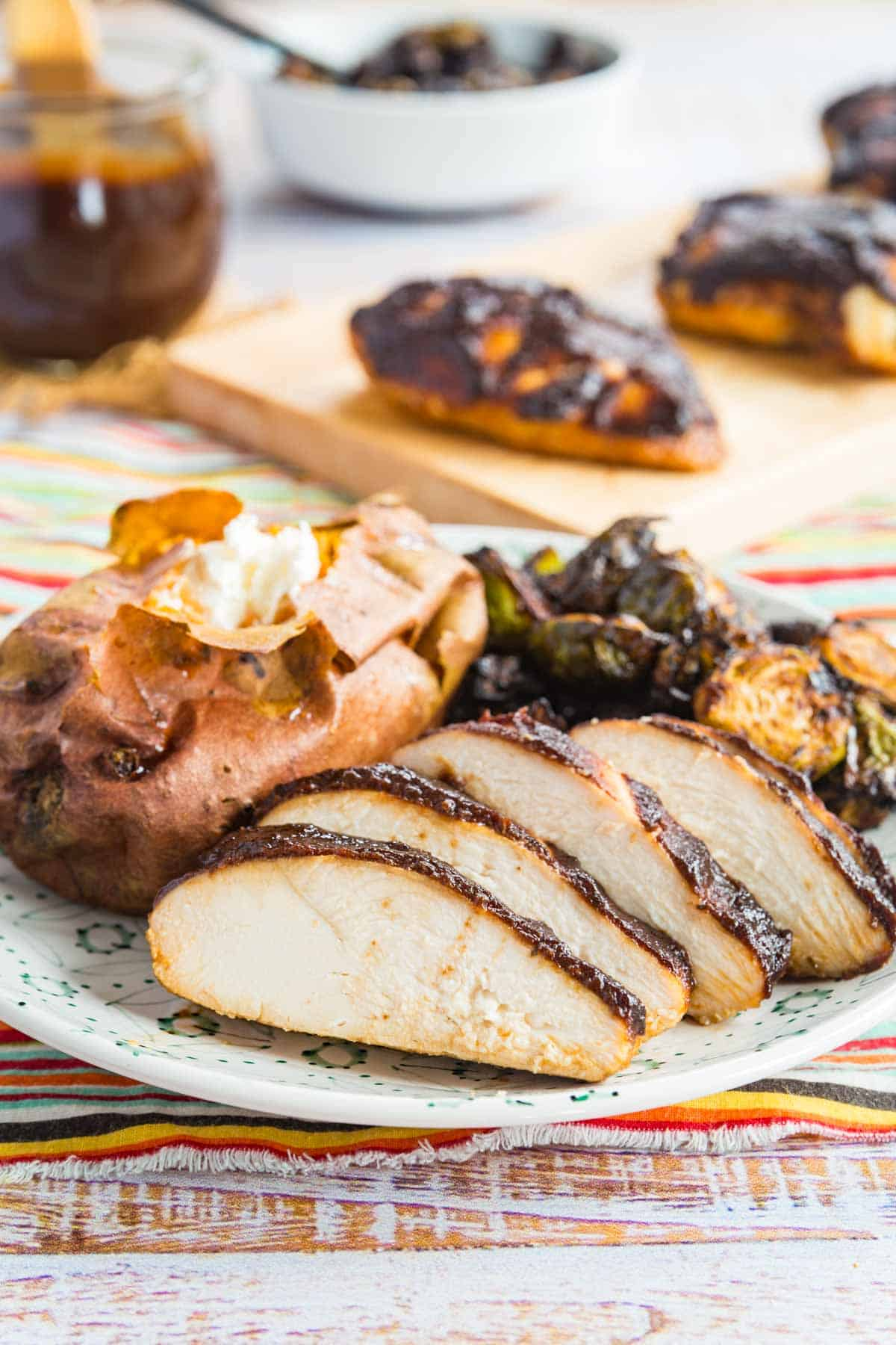 sliced of juicy chicken on a plate serve with a baked sweet potato and brussels sprouts
