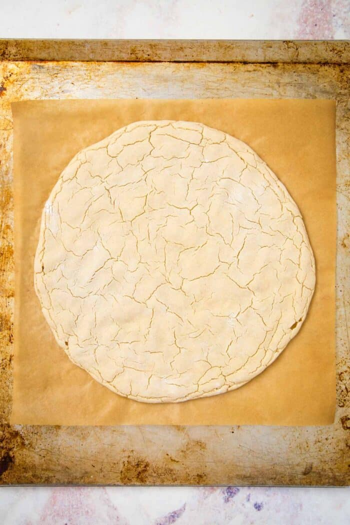 par-baked gluten free pizza crust on a baking sheet