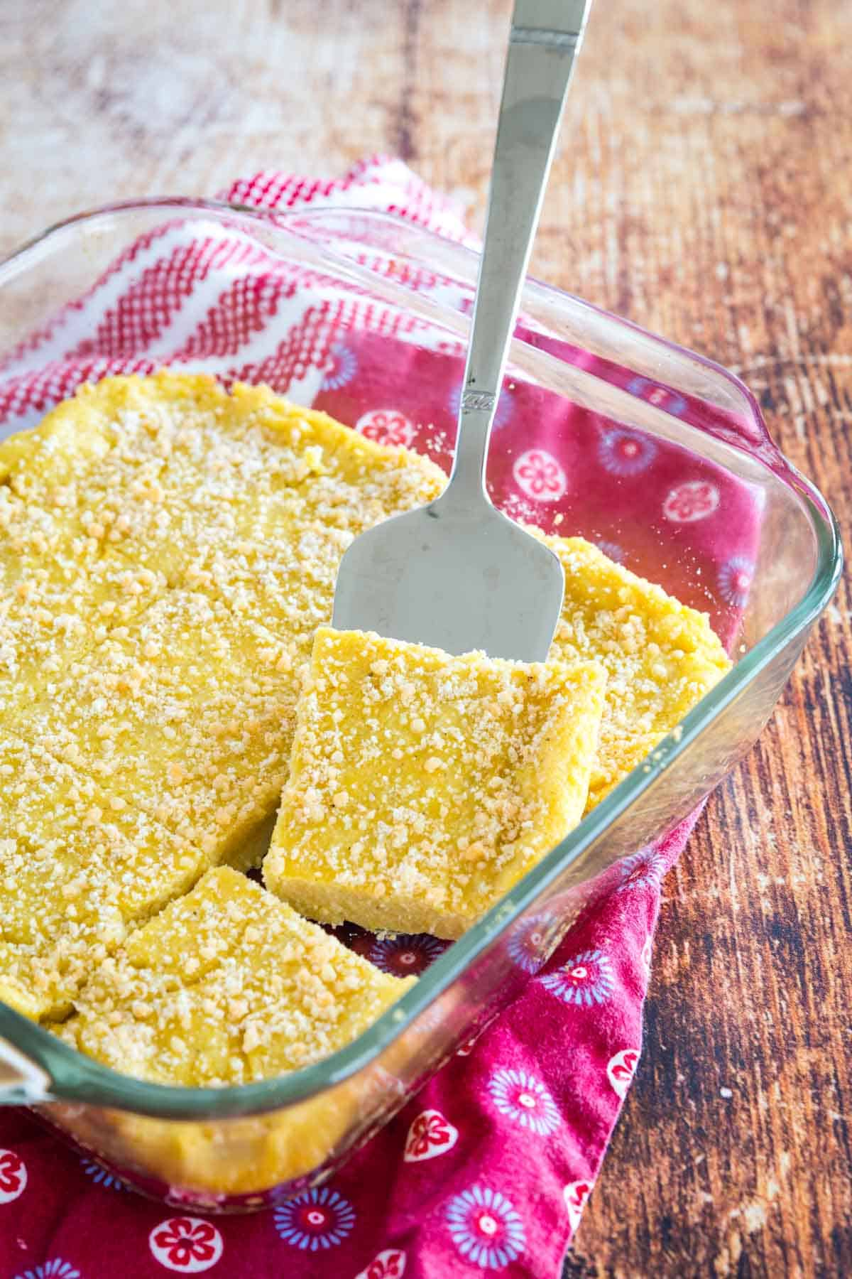 baked polenta cut into squares in a baking dish with one lifted with a serving spatula