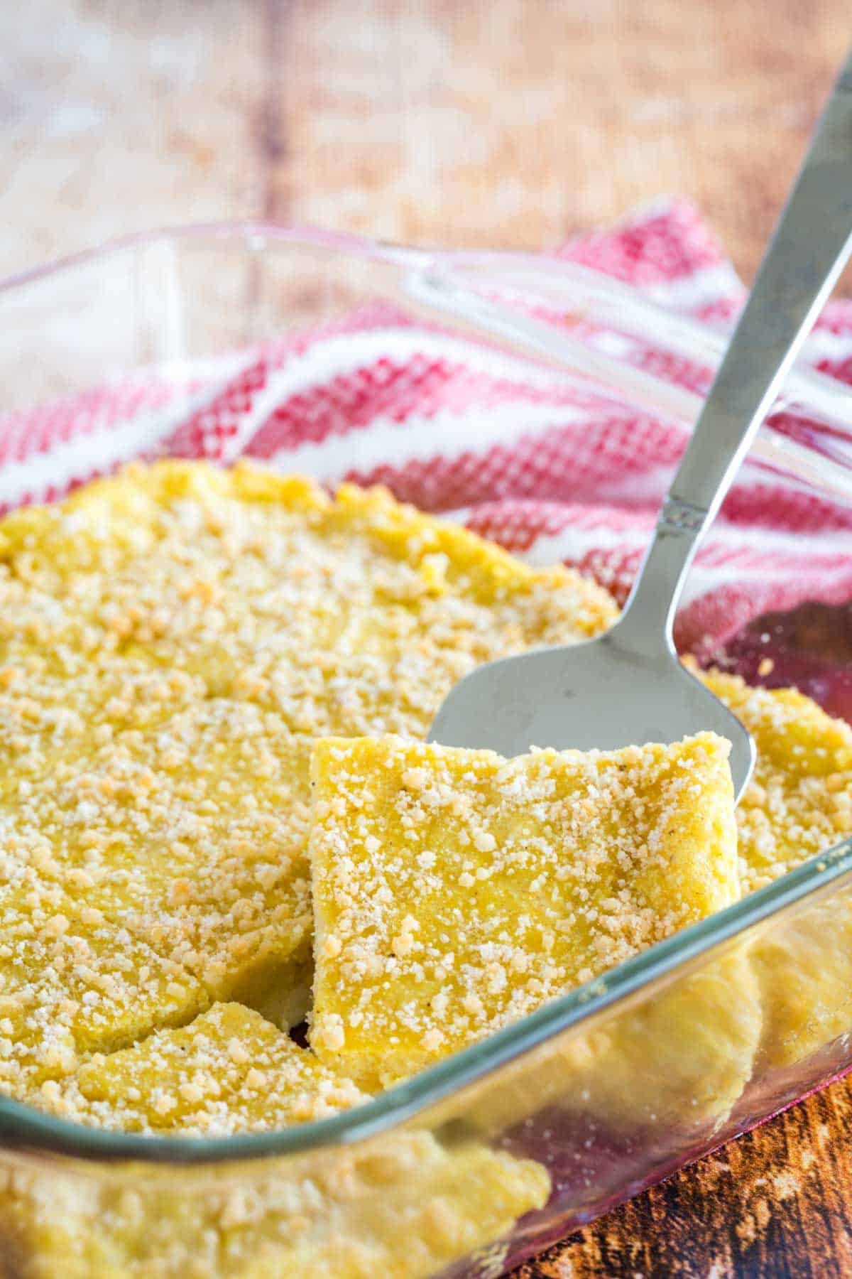 silver spatula lifting a square of baked polenta with parmesan cheese on top from a glass baking dish