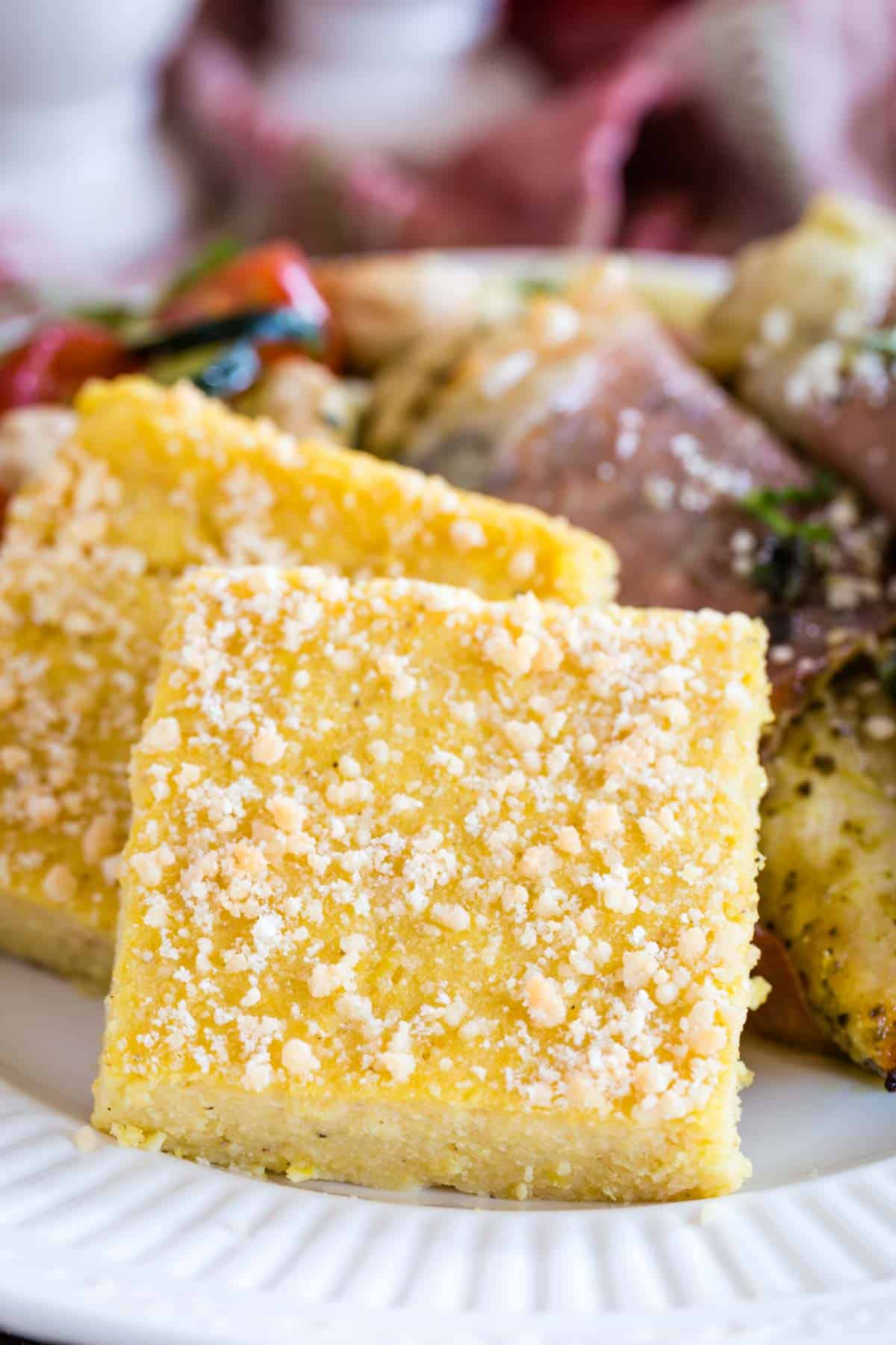 square of polenta with parmesan on top on a white diner plate