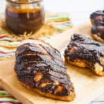 sliced baked chicken breast with balsamic barbecue sauce on a wooden cutting board