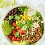 ground beef and rice bowl with taco toppings on a white table with a white napkin and squeezed lime wedges