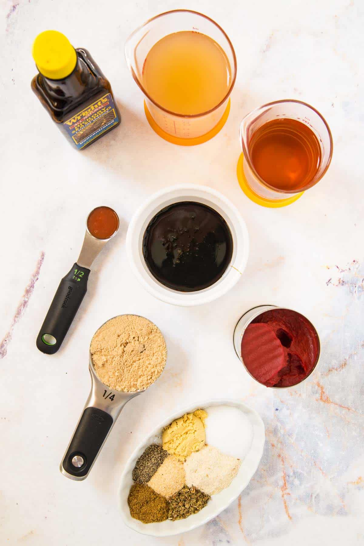 bowls and measuring cups with tomato paste, bourbon, apple cider vinegar, brown sugar, molasses, hot sauce, and different spices and seasonings, and a bottle of liquid smoke