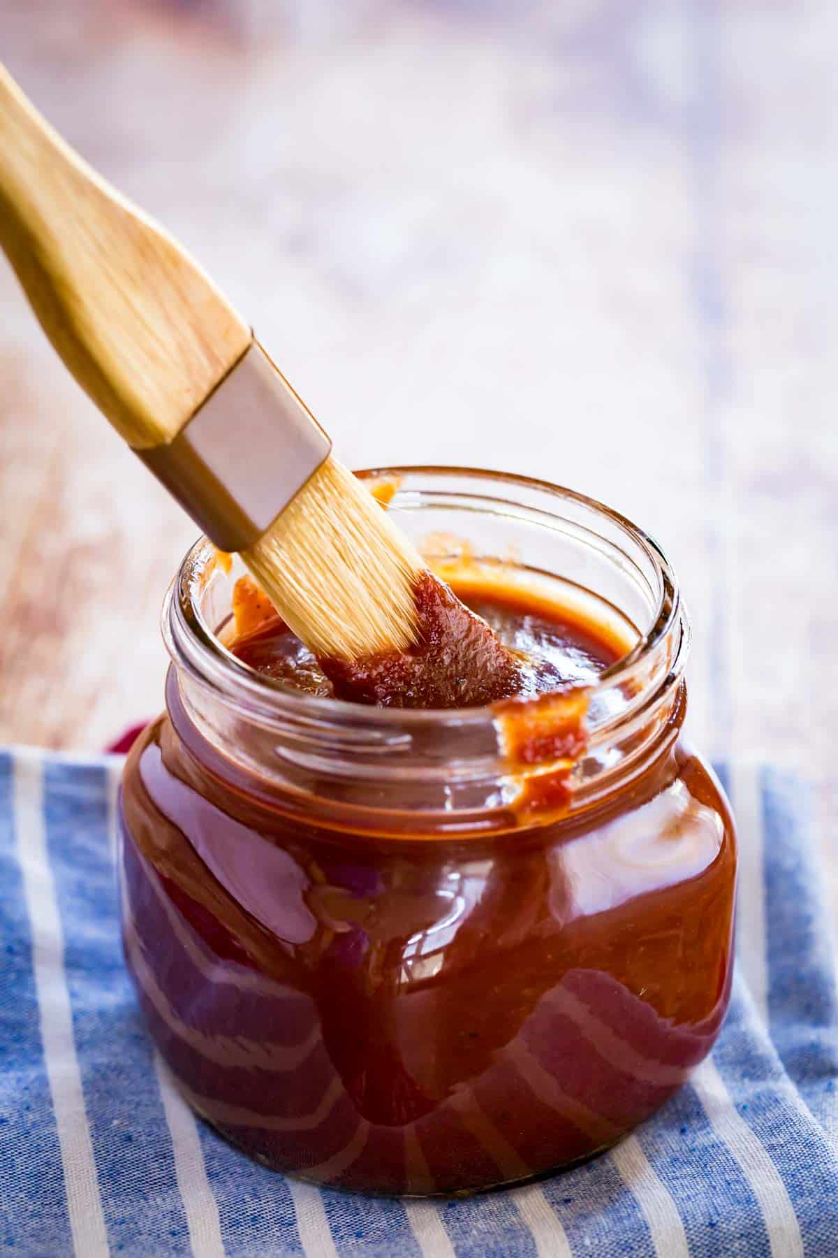 brush dunked into a glass jar of bourbon bbq on a white and blue striped cloth napkin