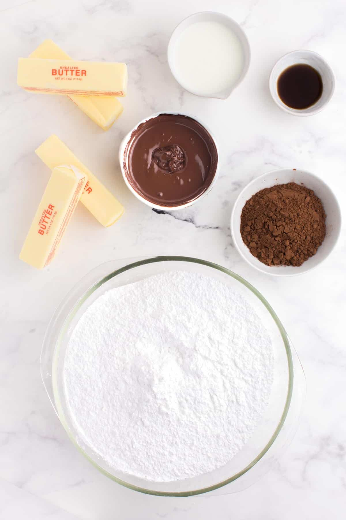 Four sticks of butter plus bowls of powdered sugar, cocoa powder, melted chocolate, vanilla extract, and buttermilk