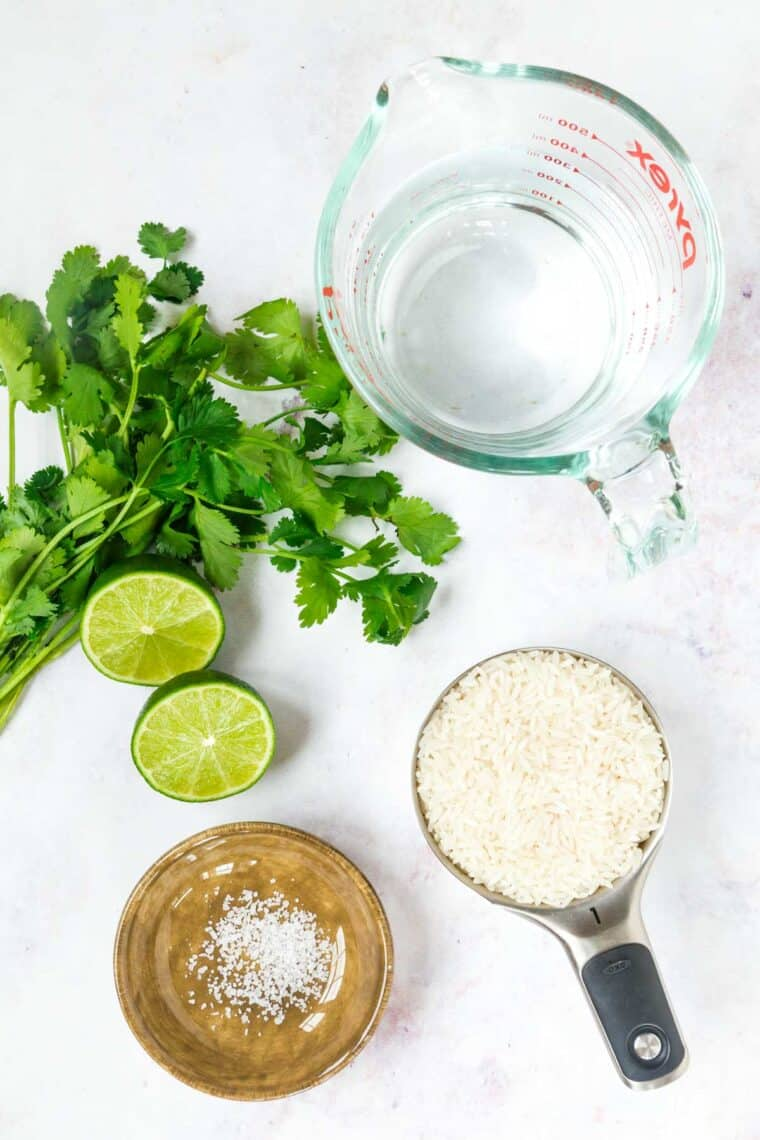 measuring cup of rice, measuring cup of water, bowl of salt, bunch of cilantro, and a lime cut in half on a marble tabletop