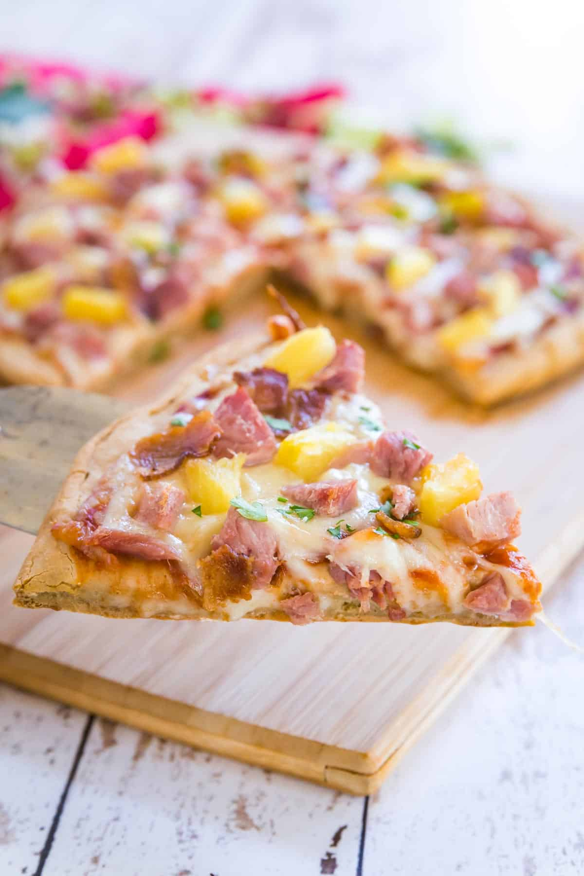 spatula holding a slice of ham and pineapple pizza