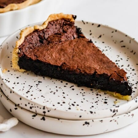 slice of gluten free chocolate chess pie on a white plate with black speckles