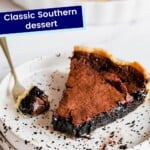 piece of gluten free chocolate chess pie on a speckled plate with a bite on a fork to the side