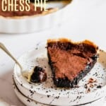 slice of gluten free chocolate chess pie on a speckled plate with a bite removed on the fork to the side