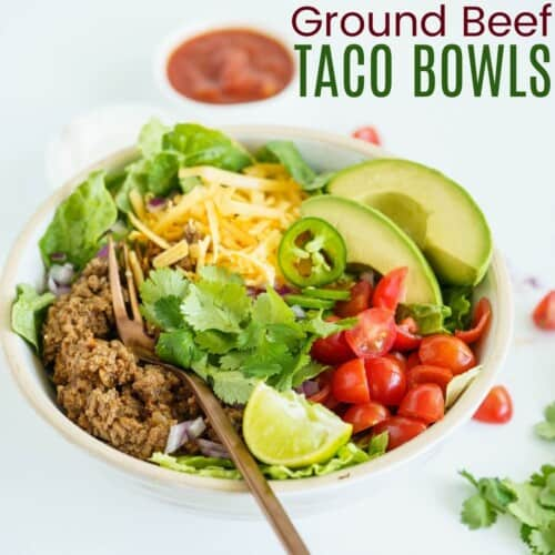bowl of lettuce topped with ground beef taco meat, tomatoes, avocado, cheese, jalapenos, and cilantro
