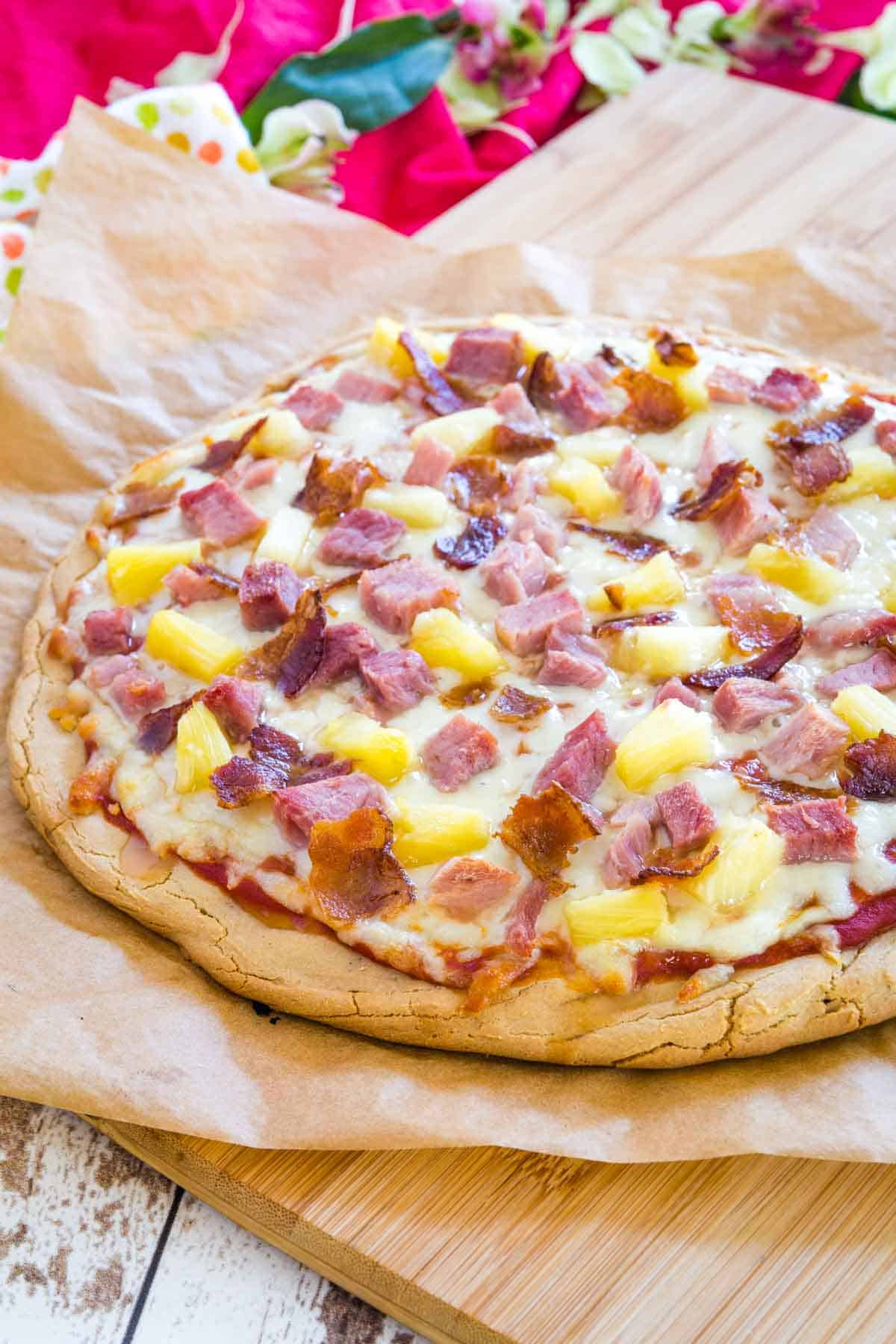freshly baked hawaiian pizza on a cutting board
