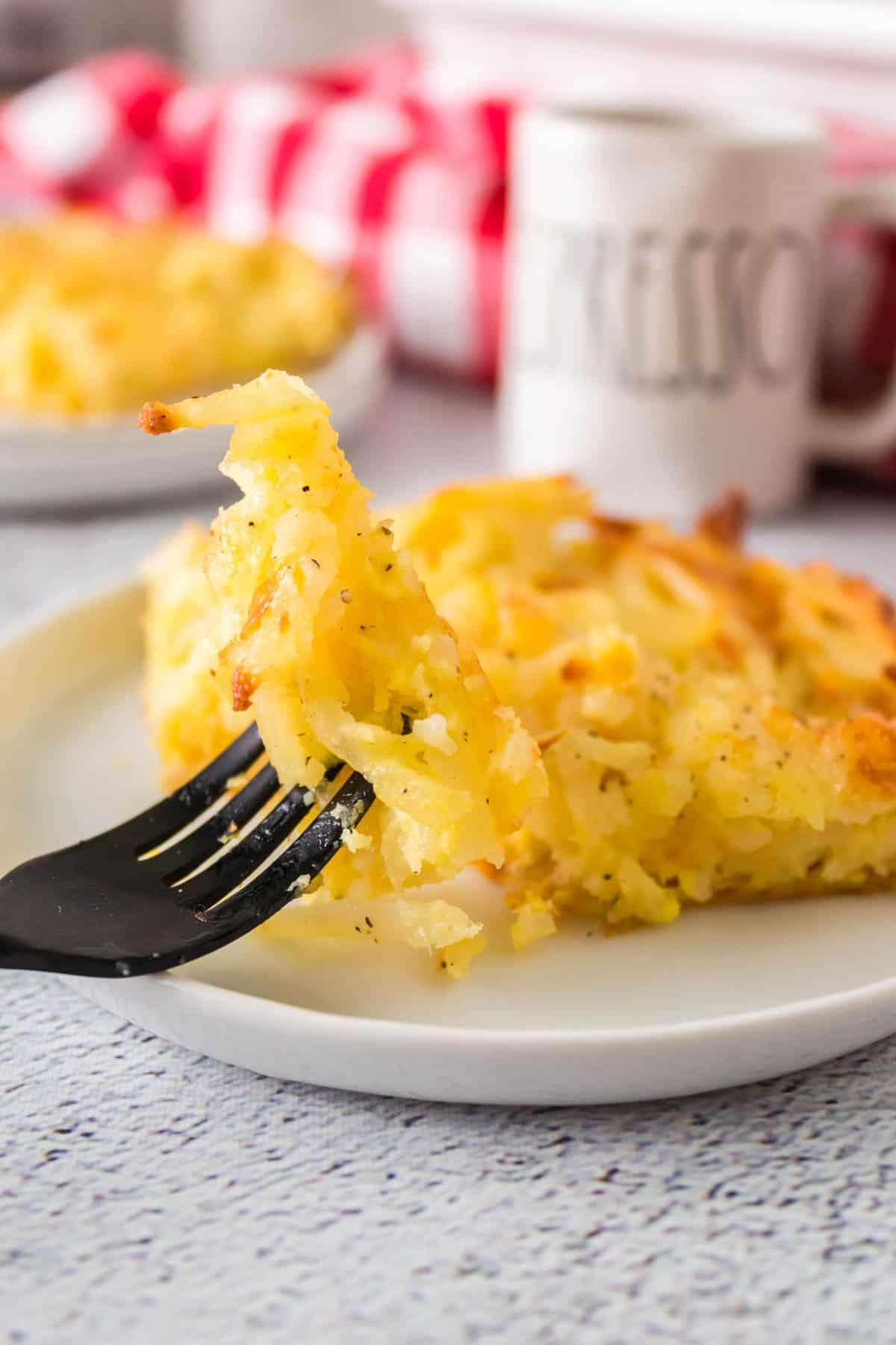 fork picking up a piece of the potato casserole on a plate