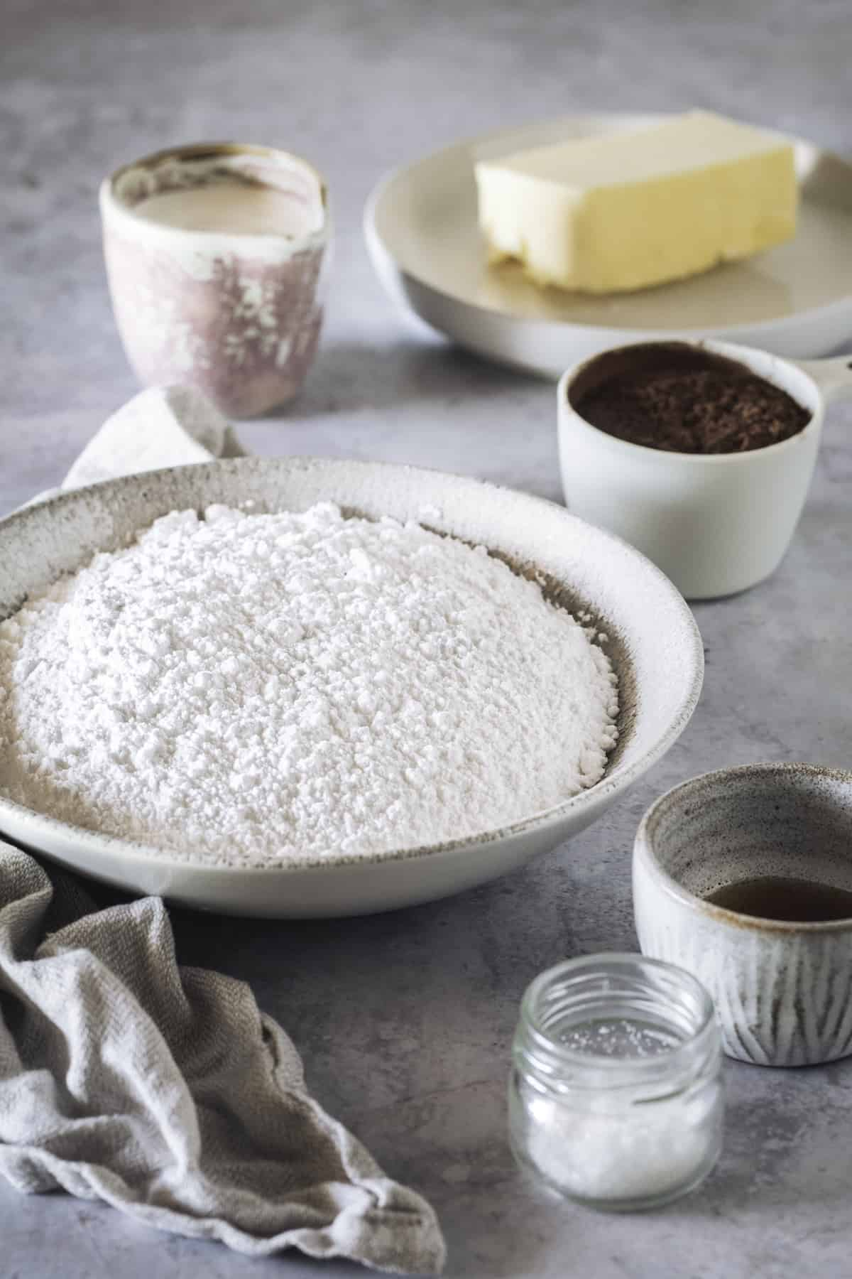 A Bowl of Powdered Sugar, Half a Cup of Butter and the Other Frosting Ingredients on a Gray Surface