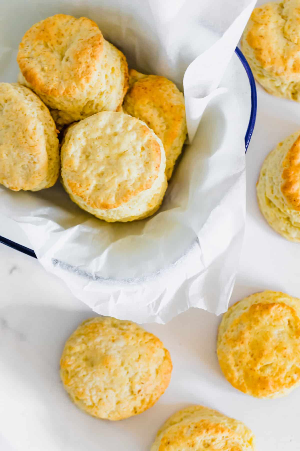Sweet Biscuits on a White Surface with More in a Parchment-Lined Bowl