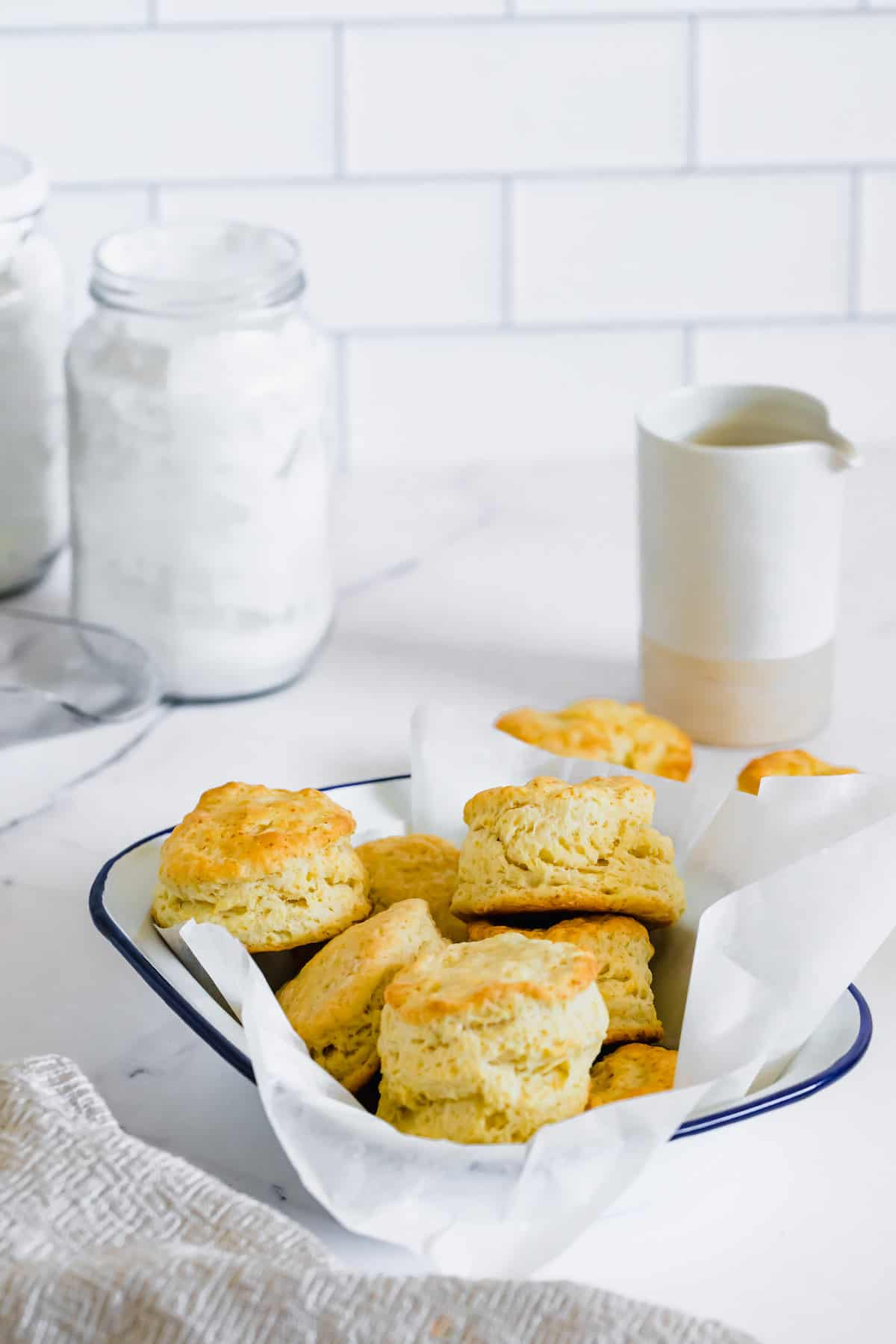 A Dish Full of Biscuits Next to a Cup of Milk and a Jar of Gluten-Free Flour