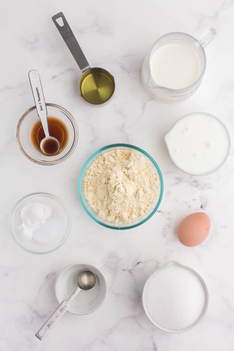 bowls of gluten free flour, sugar, milk, oil, vanilla extract, lemon extract, yogurt, baking soda, and salt on a marble table