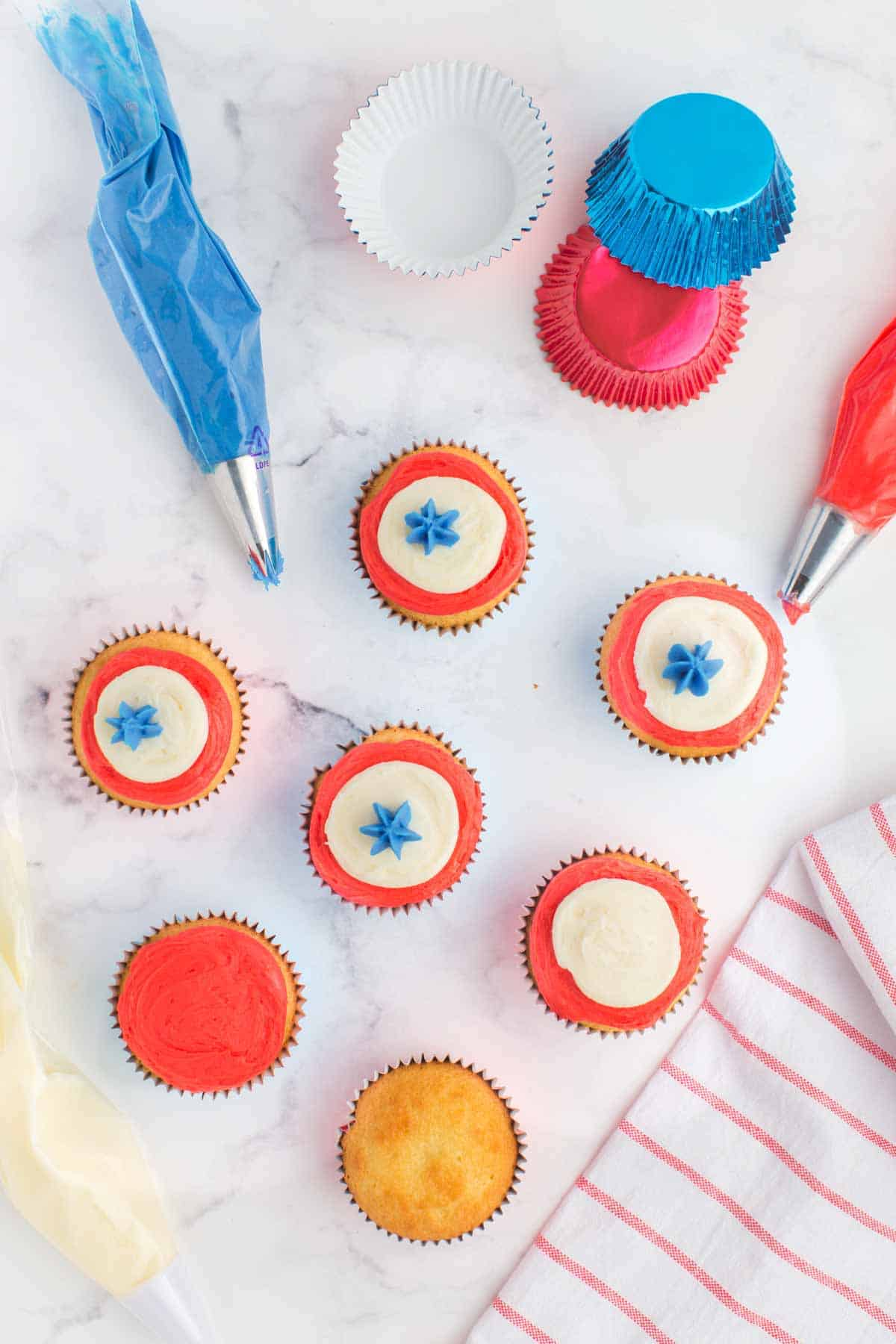 seven cupcakes at various stages of being decorated by piping red, white, and blue frosting