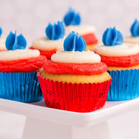 several cupcakes in red foil and blue foil wrappers with layers of red, white, and blue frosting