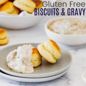two biscuits with sausage gravy over one of the on a gray plate with bowls of more biscuits and gravy in the background